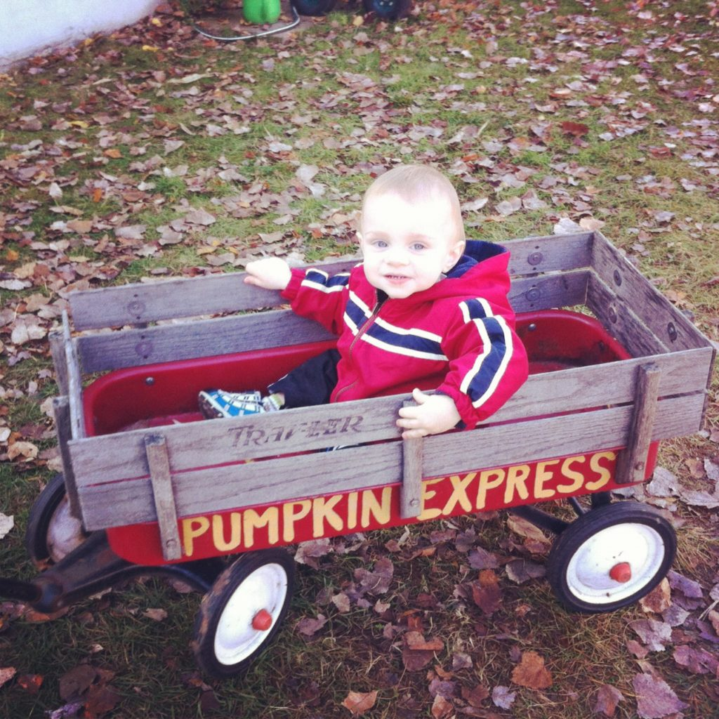 Riding in a wagon while Dada pulled him around the farm.