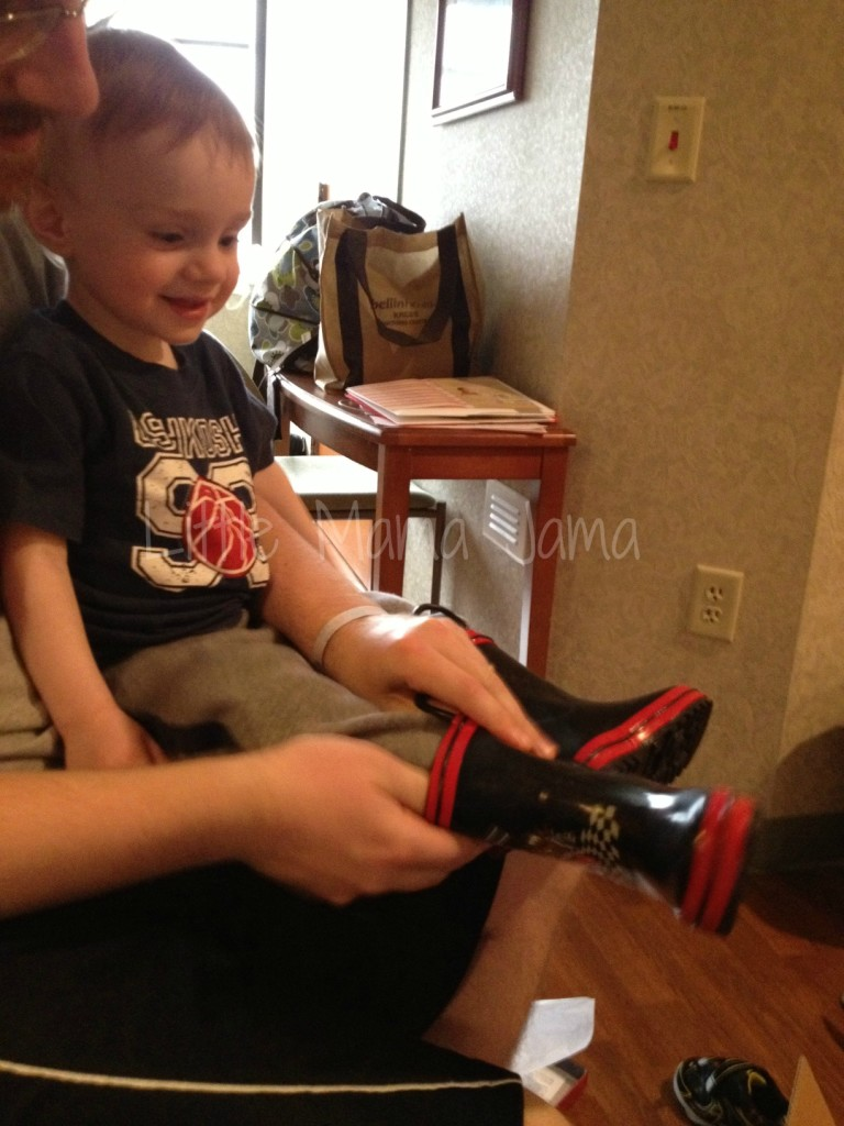 "We celebrated C's birthday with some cake. Here he is trying on his new ""Cars"" rain boots!"