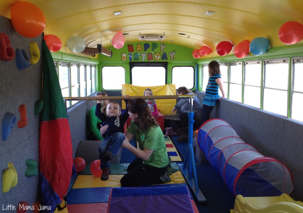 Toddler swinging from bar on Bouncin' Bus