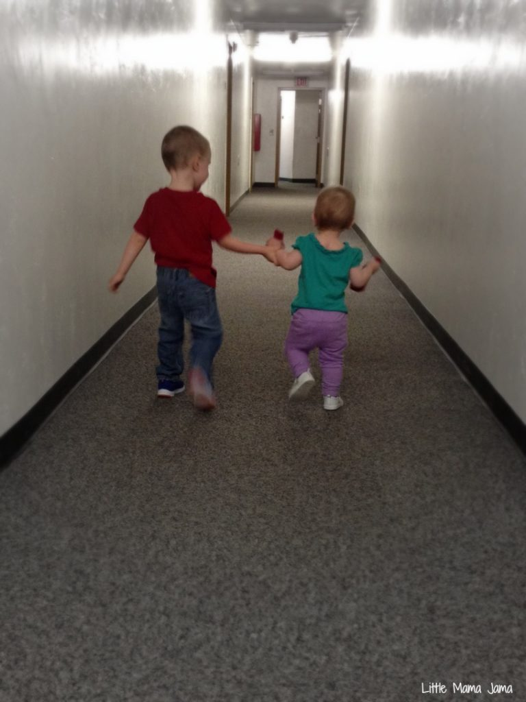 Siblings holding hands in the hallway