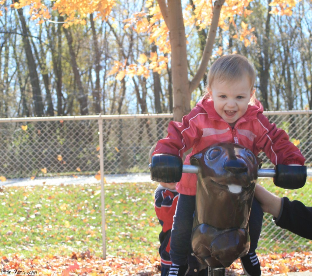 Baby Jo rides toy at park