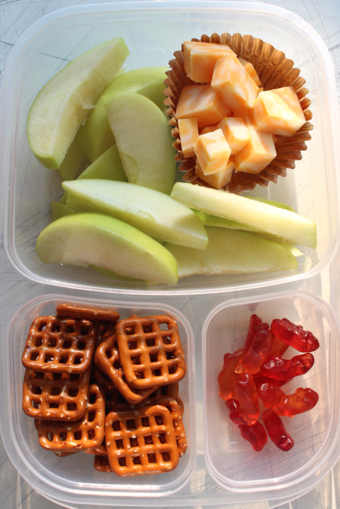 Use a bento box to create this easy, make-ahead school lunch with apple slices, cheese cubes, pretzels and fruit snacks! Click through for more school lunch ideas. [ad]